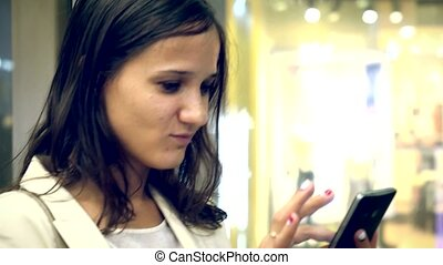 Beautiful smiles businesswoman uses mobile phone inside an elevator while moving up