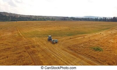 Tractor Baler Driving In Stubble Field - This is an aerial...