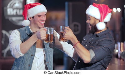 Two jolly Santa boys with glasses of beer