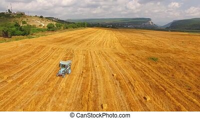 Tractor Baler Driving Along Yellow Wheat Field