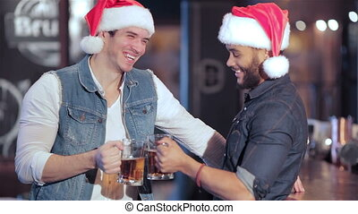 Two Jolly Santa boys with glasses of beer smiling at the...
