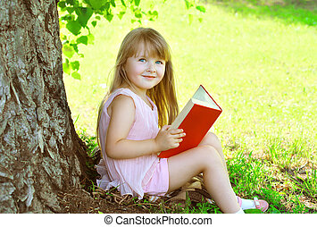 Little smiling girl child reading a book on the grass near tree in summer park