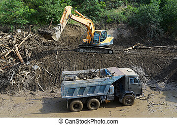 excavator clears road from landslide - excavator clears the...