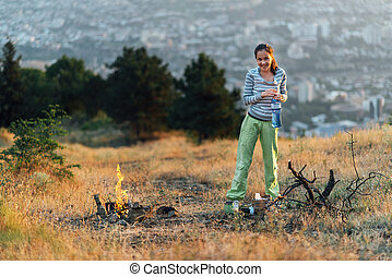 girl standing by fire on camping - girl standing by fire on...