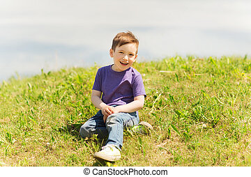 happy little boy sitting on grass outdoors - summer,...