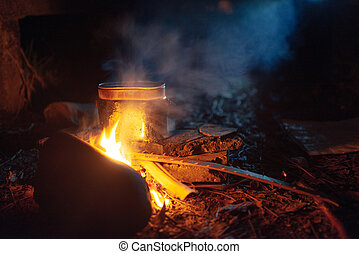 food is cooked in pot over a campfire at night - food is...