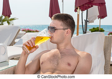 Young man enjoying a cold beer as he relaxes on a recliner...