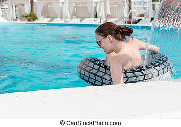 Woman with Lifebuoy Under Swimming Pool Waterfall