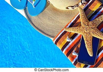 Beach hat, bath towels, cell phone, starfish, thongs near...