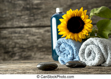 Spa still life - beautiful blooming sunflower on top of two rolled towels, two black massage stones and bottle of massage lotion