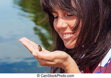 little frog in the hand of a girl