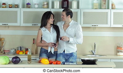Couple in love drinking grape juice and kissing in the kitchen