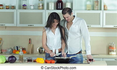 Couple preparing a vegetable stew Young smiling friends cook...