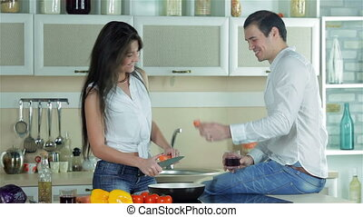 A loving couple is preparing a tasty dish for dinner