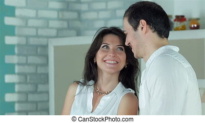 Couple looking eye to eye with tenderness while cooking dinner