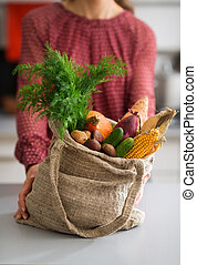 Closeup of burlap sac filled with fall vegetables with woman...