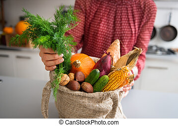 Closeup of fall vegetables and nuts in burlap bag held by...