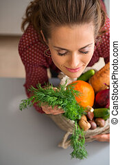 Woman with eyes closed smelling fresh fall vegetables - The...