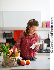 Woman in kitchen comparing shopping list to items in bag - A...