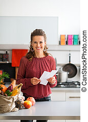 Happy woman with shopping list and bag of fresh produce - An...