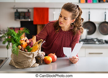 Woman in kitchen holding shopping list looking through items...