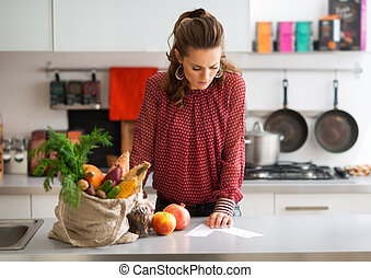 Woman in kitchen reading shopping list on counter with...