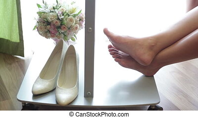 Womans shoes and bridal bouquet Leg of the bride