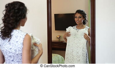 Bride trying on wedding dress before the mirror