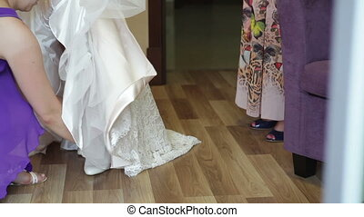 bridesmaid helps the bride to wear shoes