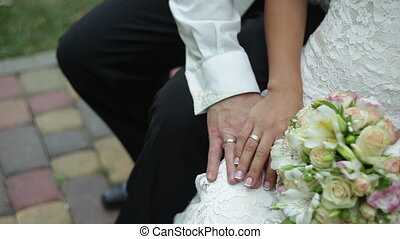 Bride caresses groom's hand near a bridal bouquet