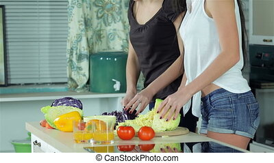 Two smiling girlfriends sliced vegetables smiling directly at the camera and show OK