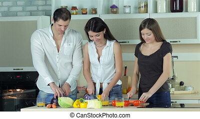 Three friends sliced vegetables for frying