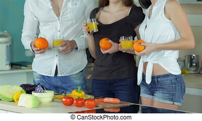 Three friends freshen up with orange juice Young smiling...