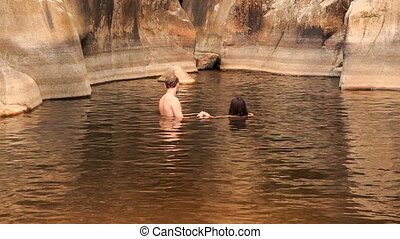 guy and girl bathe swim in warm lake created by mountain...