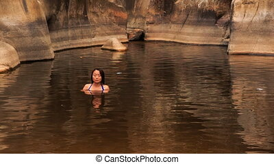 girl bathes guy comes into warm lake created by mountain stream