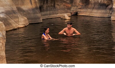guy shows to girl to swim in lake created by mountain stream...