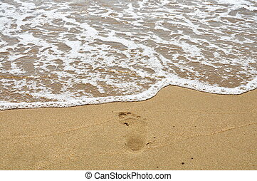 salt water flow to foot step on the beach