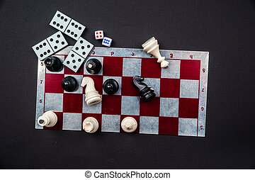 Various board games and figurines over checkers board and...