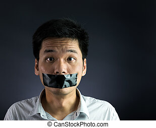 Silenced - Man with black tape over his mouth on black...