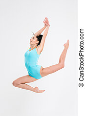 Attractive woman doing acrobatic stunt isolated on a white...
