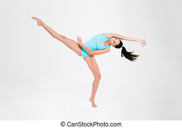 Charming young girl doing acrobatic stunt isolated on a...