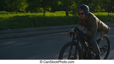 Vintage Street Racer - Hipster riding retro moped along city...