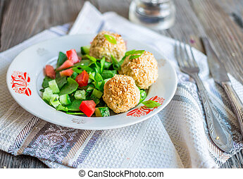 baked chickpeas balls with sesame and vegetable salad on a gray wooden,selective focus