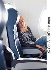 Lady traveling napping on a plain - Tired blonde casual...