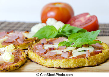 Cauliflower pizza - Closeup of small round baked pizza made...