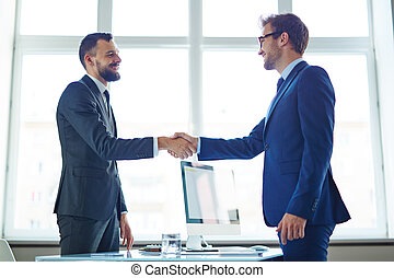 Business deal - Confident businessmen handshaking over...