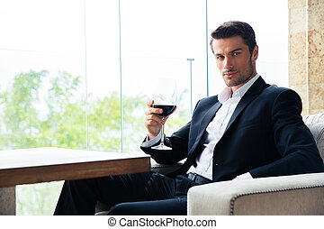 Businessman sitting at restaurant with glass of wine -...