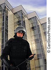 riot policeman with office building behind