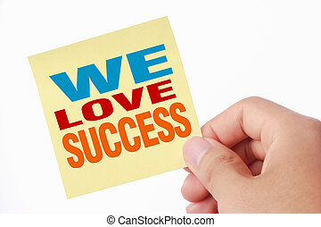 We love success - Hand holding the yellow sticky note with...