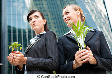 Businesswomen with Plants - Two competitive businesswomen...